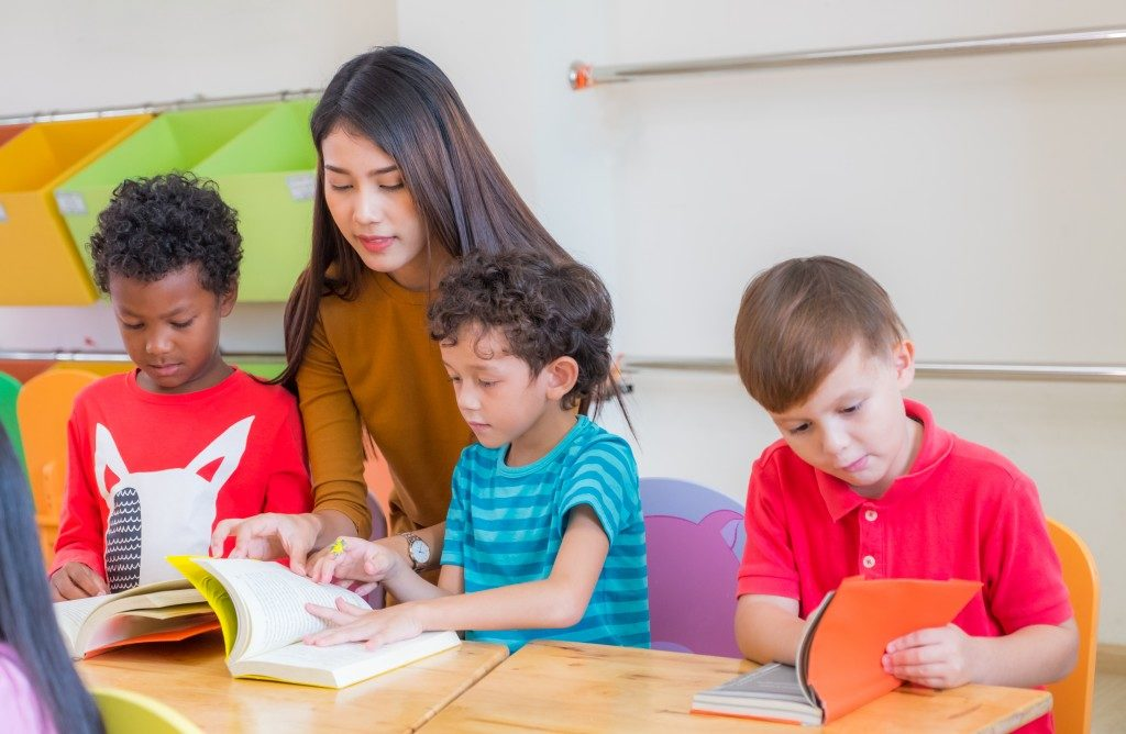 woman teaching kids how to read