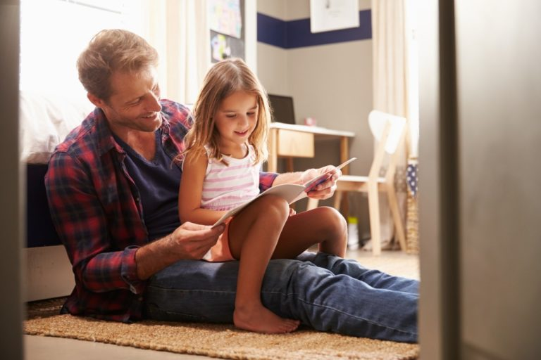 father teaching his daughter to read