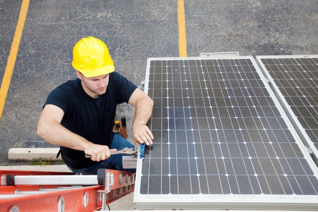 a blue collar worker installing a solar panel