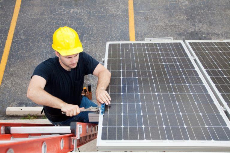 a blue collar worker installing a solar panel
