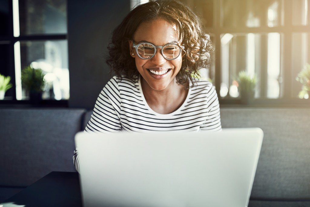 woman smiling in front of her laptop