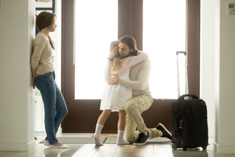 Child hugging father as he leaves with mother on the side