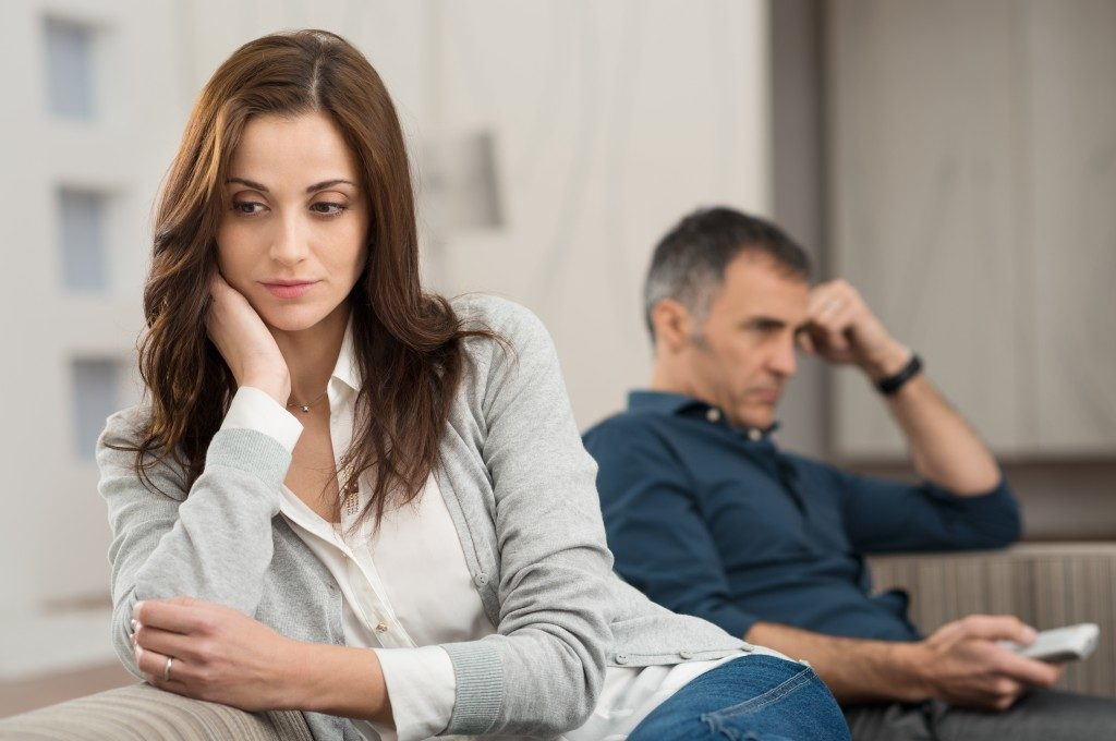 unhappy woman sitting beside her husband