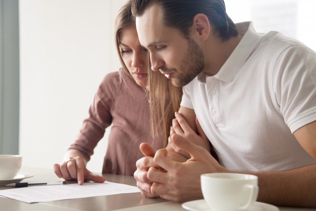 couple looking at paper over coffee