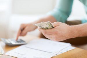computing bills in man's hand