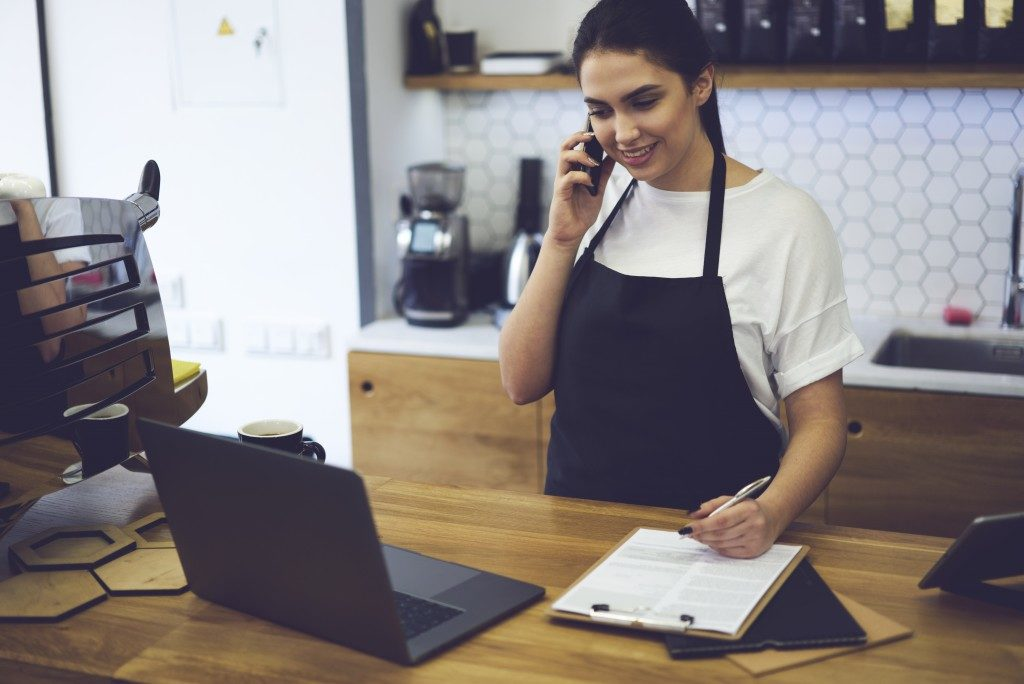 Beautiful skilled entrepreneur dressed in black apron with mock up making coffee business by herself. Smiling barista standing at bar and talking with web consultant about ordering food for cafeteria
