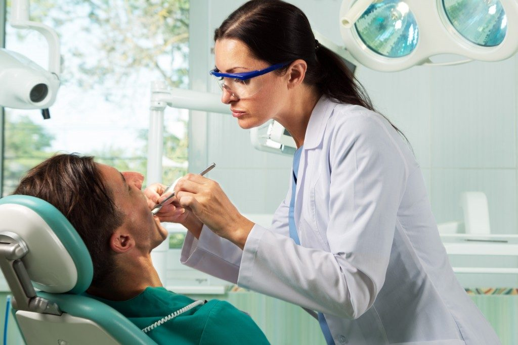 Dentist cleaning patient's teeth