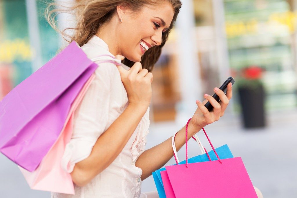 woman on her phone carrying shopping bags