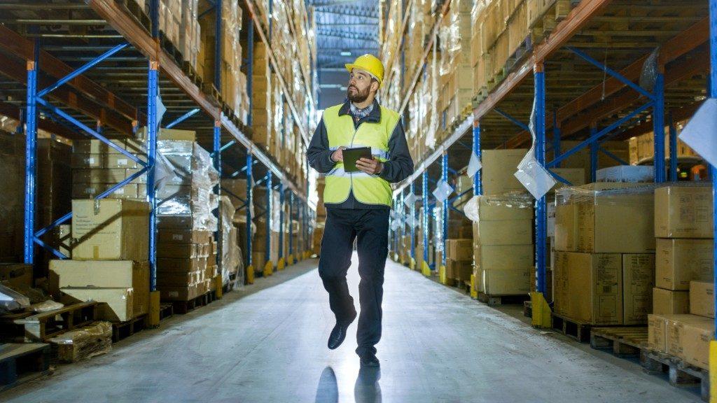 man in safety gear walking inside the warehouse