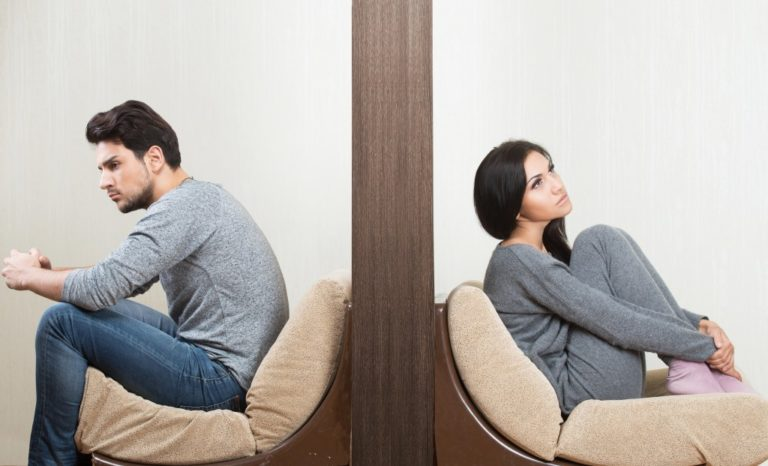 troubled couple sitting apart