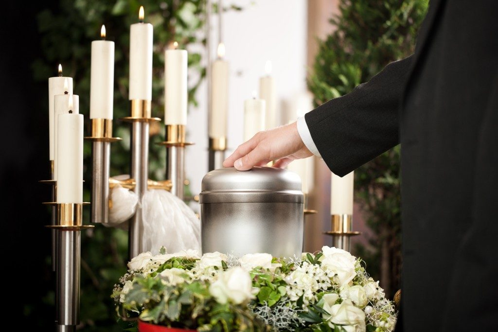 mortician carrying the urn to a bed of white roses