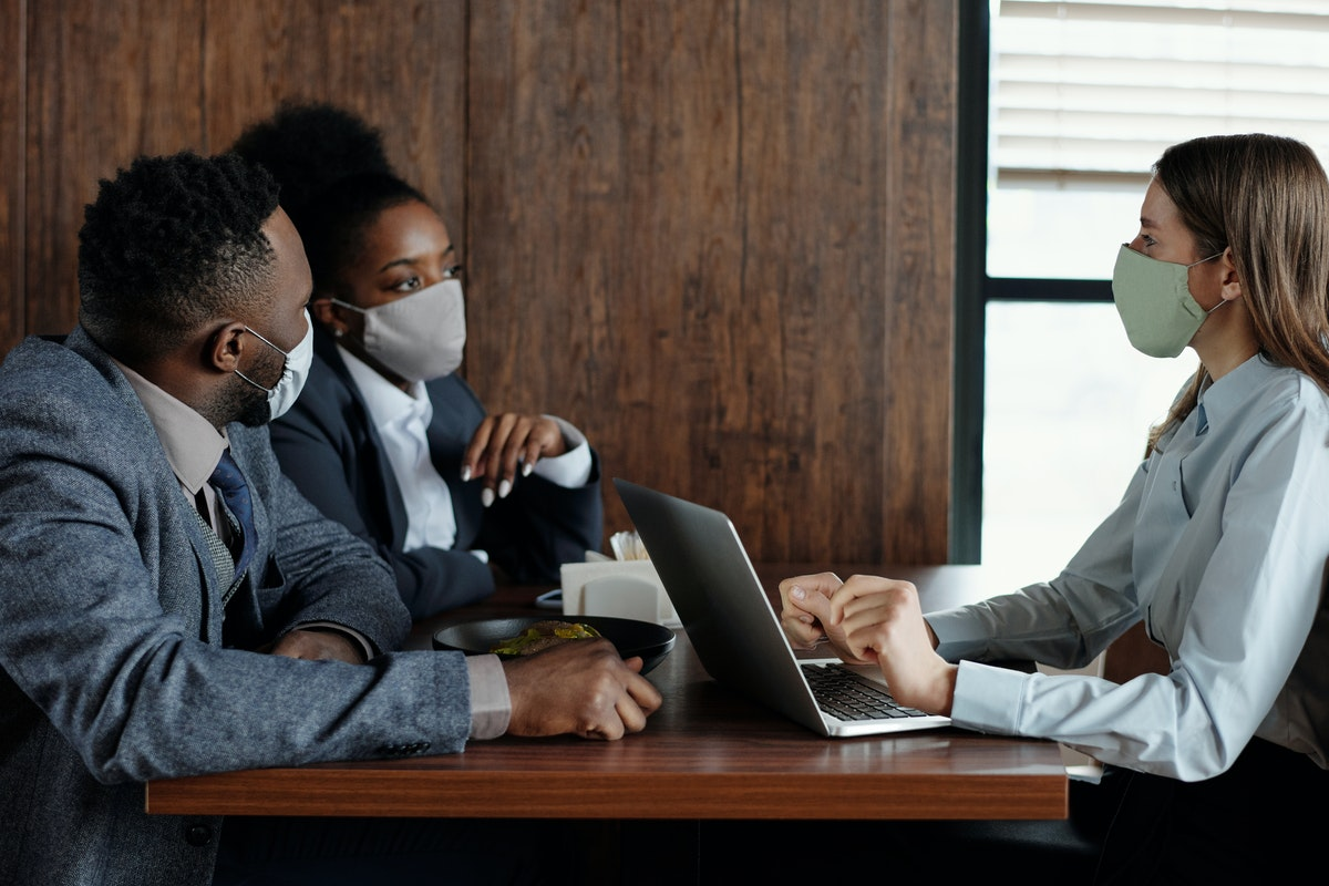 paralegals having a meeting wearing facemask